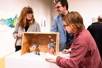 "Cole Pruitt and Rachel Kalman (left) interact with the exhibit he created with Lara Head titled ""Freedom of Assembly"" while Sara Weininger looks on at the Parabola: Assembly exhibition, Des Lee Gallery, Washington University, St. Louis, MO"