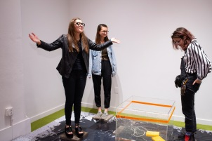 "from left, Libby Evan, Alessandra Ferrari-Wong, and Zoe Finkelstein interact with""30minutes"" by Megan Jiyoung Lee at the BFA 2 Show on display at the Des Lee Gallery, Washington University, St. Louis, MO"