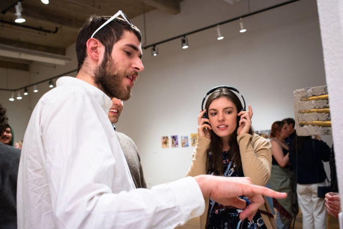 "Antonio Leone (left) listens to the piece "".50 Caliber Coat Check"" by Merry Sun while Robert and Samantha Orf look on, BFA Show 2, Des Lee Gallery, Washington University, St. Louis, MO"