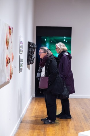 "Beverly Knight (left front) and Sarah Jakle view ""Fukushima Flowers"" by Takura Suzuki on display at the Parabola: Extraterrestrial Exhibit, Des Lee Gallery, Washington University, St. Louis, MO"