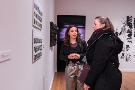 "Sarah Knight (c) talks with Beverly Knight while they view ""Fukushima Flowers"" by Takura Suzuki on display at the Parabola: Extraterrestrial Exhibit, Des Lee Gallery, Washington University, St. Louis, MO"
