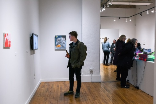 "Joe Whalen watches ""Sweet Jane (Live) at the Matrix, November 27, 1969"" by Chris Scott on display at the Parabola: Extraterrestrial Exhibit, Des Lee Gallery, Washington University, St. Louis, MO"